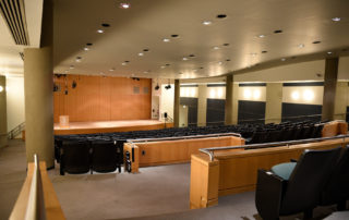 Proshansky Auditorium - Auditorium Rental in NYC. View from back of the auditorium - stage, seating, and handicap accessible space.
