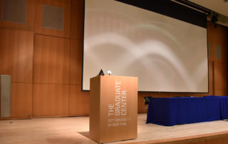 Proshansky Auditorium - Auditorium Rental in NYC. Stage set up for a presentation with podium, screen, and table for panelists.