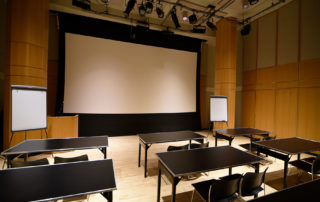 Segal Theatre - Black Box Theater Rental in NYC. Set up classroom style, looking towards front of the theater space.